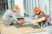 image of overhauling  - Two industrial tiler builder worker installing floor tile at repair renovation work - JPG