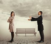 stock photo of repentance  - young man apologizing to woman at outdoor - JPG