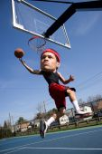 stock photo of bobble head  - A basketball player with a large head driving to the hoop with some fancy moves - JPG
