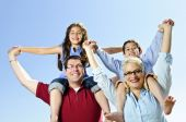 stock photo of family fun  - Happy family having fun giving shoulder rides - JPG