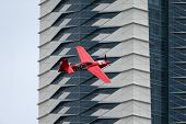 PUTRAJAYA, MALAYSIA - MAY 17, 2014: Pete McLeod of Canada, in an Edge 540 V3 plane flies past the skyscrapers of Putrajaya at the qualifying session of the Red Bull Air Race World Championship 2014.