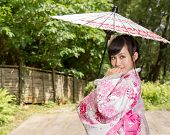 Asian Woman Wearing A Kimono Sitting In Japanese Garden
