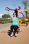 Woman Exercising With Lat Pull Fitness Machine