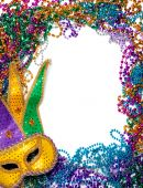 stock photo of tuesday  - A border made of a gold purple and green mardi gras mask and blue green red gold and purple plastic beads - JPG