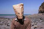 Man With Paperbag Over His Head On The Beach