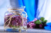 Beautiful lilac flowers in glass jar, on color wooden table, on bright background