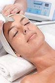 Closeup portrait of young woman receiving facial beauty treatment.