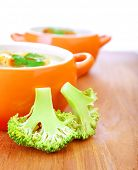 Two bowl with creamy soup on wooden table in dinning room, fresh green broccoli, organic nutrition,