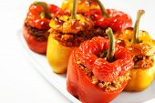 A picture of red and yellow stuffed peppers baked and served on a white plate