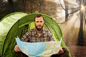 Handsome traveler near tent with a map planning route in autumnal forest