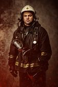 foto of firefighter  - Firefighter with helmet and axe in a smoke - JPG