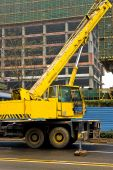 stock photo of boom-truck  - Yellow and black telescopic crane control cabin and gib arm closeup - JPG