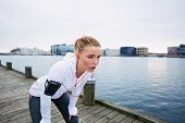 stock photo of bent over  - Female runner standing bent over and catching her breath after a running session along river - JPG