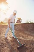 Golfer raking bunker in early morning with sunrise