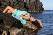 Pretty young woman in a green chiffon dress on a beach rock