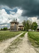 Countryside landscape with old little wooden church against dramatic sky
