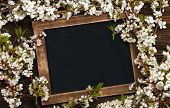 stock photo of dainty  - Old blank vintage school slate or chalkboard lying on an old rustic wooden background with dainty white flowers in two corners ready for your text or message - JPG
