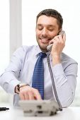 business, office and technology concept - smiling businessman with telephone dialing number at office