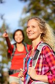 Woman hiker portrait in forest. Hiking girl smiling happy on hike living healthy active outdoor lifestyle. Beautiful young aspirational blonde female hikers wearing backpack in nature.