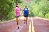 Running couple training outdoors on road in wood for marathon. Mixed race pretty young female and fit caucasian handsome man in their twenties. Lifestyle full figure
