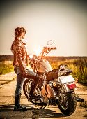 RUSSIA-JULY 7, 2013: Biker girl and bike Harley Sportster. Harley Davidson sustains a large brand co