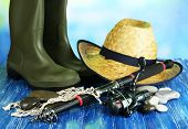 Fishing rod, gumboots and hat on wooden table on natural background