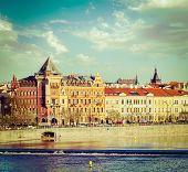 Vintage retro hipster style travel image of Prague Stare Mesto embankment view from Charles bridge on sunset. Prague, Czech Republic