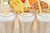 stock photo of milk products  - Banana and almond milk smoothie in a glass on a kitchen table. Summer drink made of banana almond milk and few dactyl.