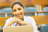 close up portrait of indian college girl with notebook computer in lecture hall