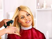Woman at hairdresser with iron hair curler.