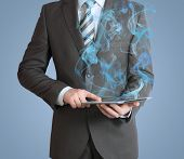 Businessman in a suit holds tablet pc with smoke