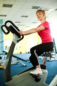 Sporty Cute Girl Exercising On The Bicycle In The Gym