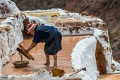 MARAS, PERU - JULY 23, 2013: woman working at Maras salt mines in the peruvian Andes