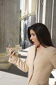 shocked businesswoman at smartphone