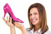 Elegant brunette admiring a shoe on white background