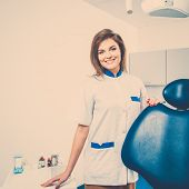 Young beautiful brunette female dentist at dentist's surgery