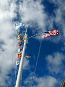 stock photo of wispy  - Nautical and American Flags Flying from a Ship - JPG