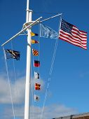 Nautical And American Flags Hanging From A Ship's Mast With Wispy Clouds