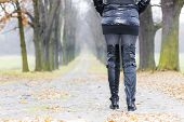 detail of woman wearing black clothes and boots in autumnal alley