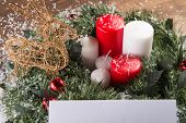 picture of deer family  - Christmas decoration   like wicker iron deer at red and white candles  and fir branches in snow with selective focus and copy place - JPG