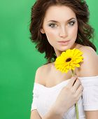 closeup portrait of attractive  caucasian  woman brunette  studio shot lips  face hair head and shoulders looking at camera skin makeup yellow flower aroma spring summer