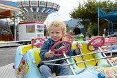 A Little Boy Playing In A Fun Fair Carousel
