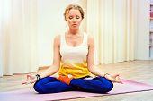 Beautiful athletic girl doing yoga exercises indoor. Lotus pose. Meditation.