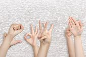 Young people's hands on grey background