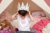 stock photo of toddlers tiaras  - Toddler child kid engaged in pretend play with princess crown and teepee tent - JPG