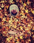 a man with a rope wrapped around his head laying in a pile of leaves toned with a retro vintage instagram like filter effect