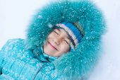 Happy Kid Girl Child Outdoors In Winter Lying On Snow Under Snowfall And Snowflakes Cover Her Face