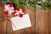 Christmas gift boxes and blank greeting card over wooden background with snow fir tree