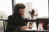 Pensive Woman In Black Working In Cafe