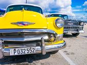 HAVANA,CUBA - OCTOBER 31,2014 : Colorful yellow vintage car parked near other classic cars with a blue sky and puffy clouds